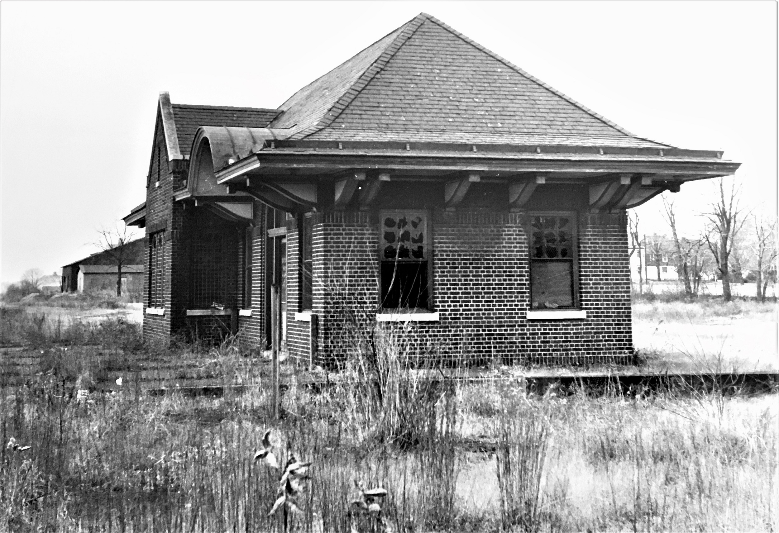 Black and white photograph of the side view of Plainsboro Station from 1967. The station building is made of brick and has a hipped roof.
