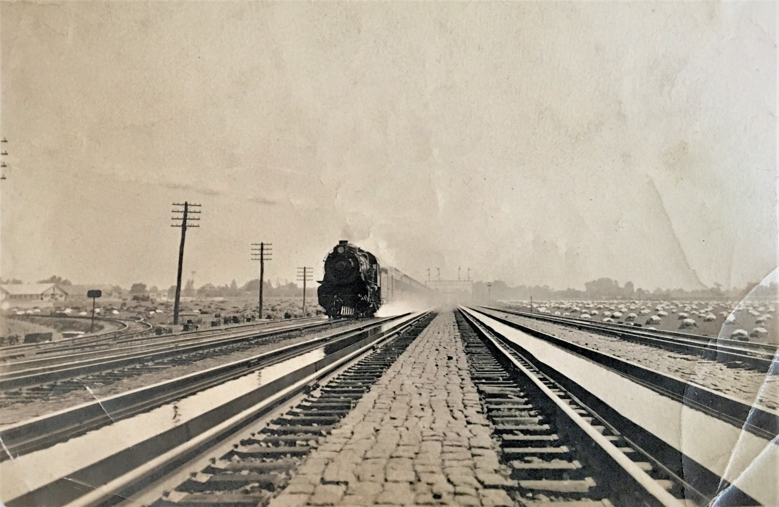 Black and white photograph of a train coming towards the viewer to the left.