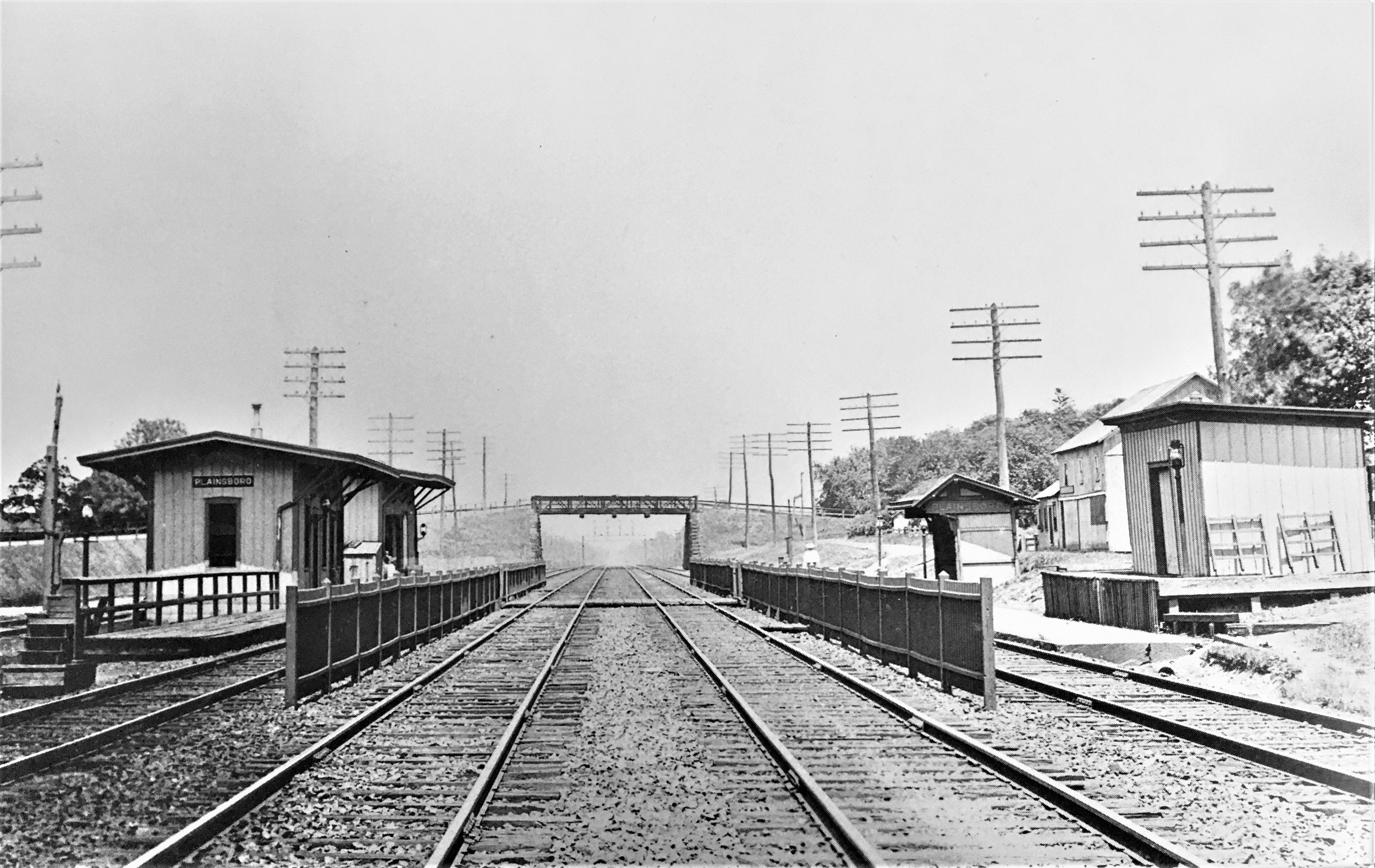 Black and white photograph of Plainsboro Station. There are four sets of train tracks. There are wooden platforms on either side with wooden buildings. A bridge crossing over the tracks is seen in the distance.