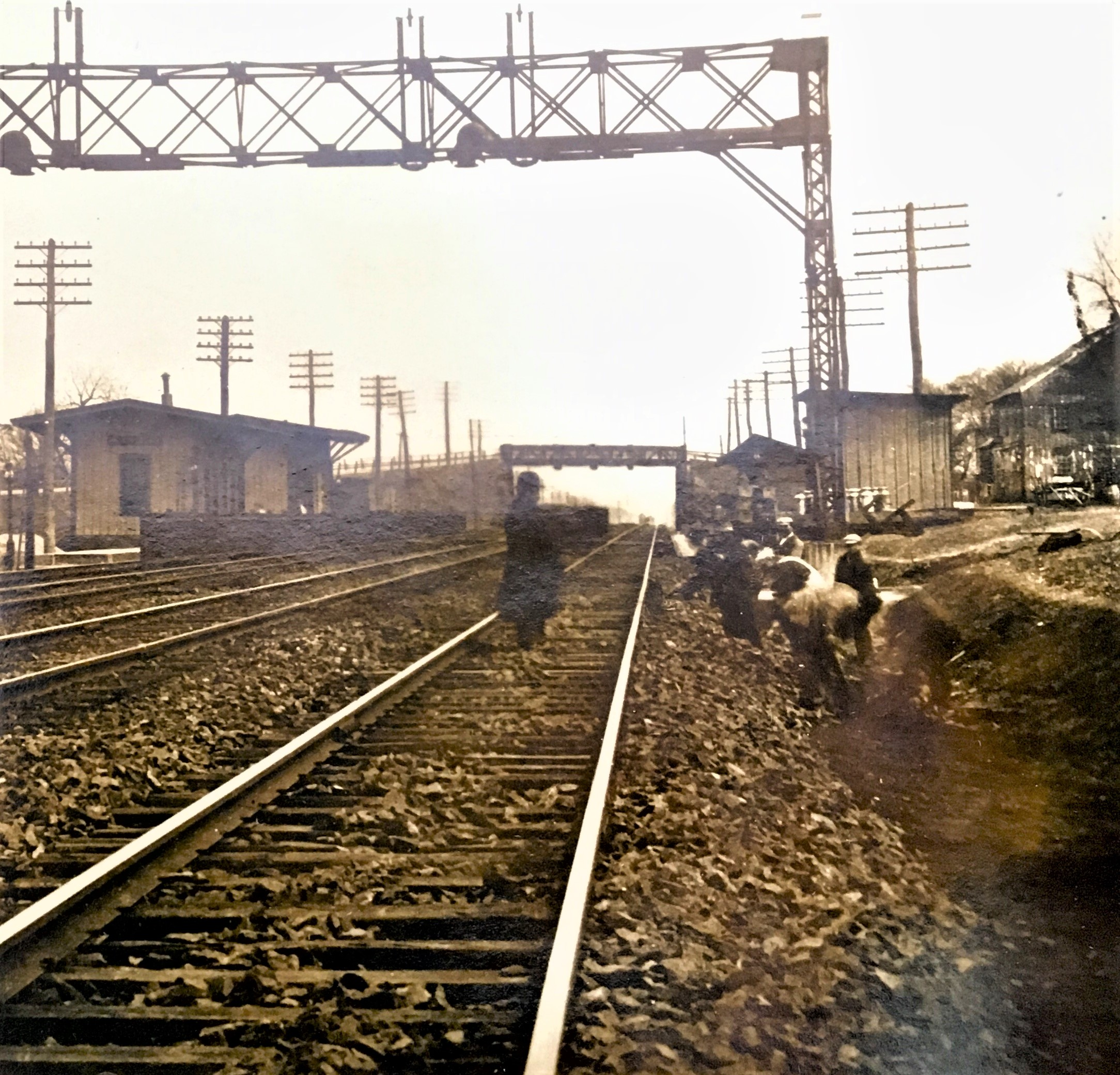 Sepia photograph of Plainsboro Station in 1915. In the center is a man standing on the railroad tracks, facing right. To the right of the tracks are several men working in a trench. Behind the men and on the left side of multiple tracks are wooden buildings. In the background is a bridge crossing over the tracks.